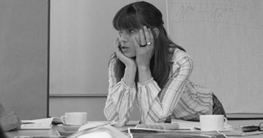 Elke Barbara Bachler (im Gespräch, auf Tisch lehnend)